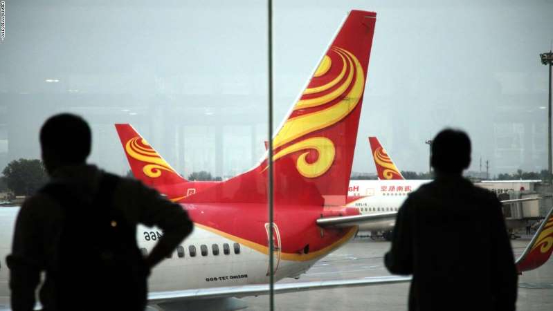 a man standing in front of a plane: Passengers look at planes belonging to China's Hainan Airlines at the gate at Haikou airport in south China's Hainan province on June 12, 2014.