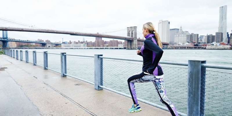 a person standing on a sidewalk: Follow these everyday running motivation tips for a fitter, healthier, and happier new you.