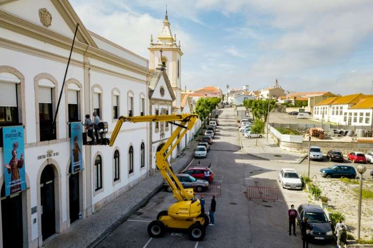 a yellow car parked on the side of a building: A manlift crane enables relatives to 'visit' elderly residents of Santo Antonio retirement house in Figueira da Foz