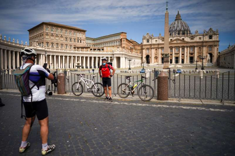 Cyclists take photos in an empty St. Peter's Square, due to anti-coronavirus lockdown measures, at the Vatican, Sunday, May 10, 2020. Pope Francis is calling on leaders of European Union nations to work together on the social and economic consequences of the COVID-19 pandemic. After delivering his Sunday blessing, Francis noted that 70 years have passed since Europe began the challenging process of reconciliation of the continent's peoples after World War II. (AP Photo/Andrew Medichini)