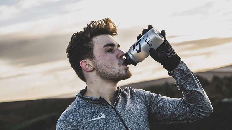 a man holding a camera: best supplements for runners