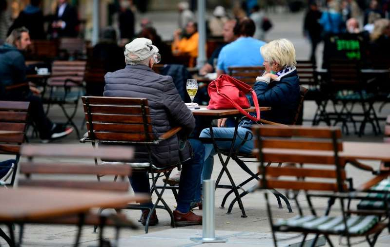 a person sitting on a bench: A couple sits in a reopened restaurant at the Alter Markt place in Dortmund, western Germany on May 12 amid the ongoing coronavirus pandemic