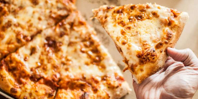 a close up of a slice of pizza: There's an easy way to make pizza you order in more delicious (and even a little nutritious). It involves breaking out a few extra ingredients you already have.