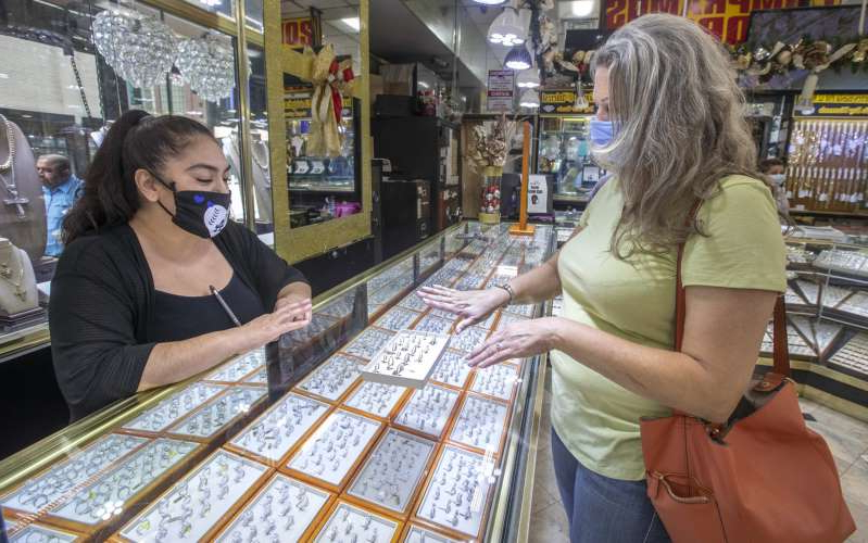a woman standing in front of a store: Lori Rand of West Los Angeles, left, tries on a ring while being helped by Mary Perez, a salesperson at High Class Jewels on Broadway in downtown Los Angeles on May 18, 2020. The jewelry store re-opened over the weekend after being forced to close due to the coronavirus outbreak.
