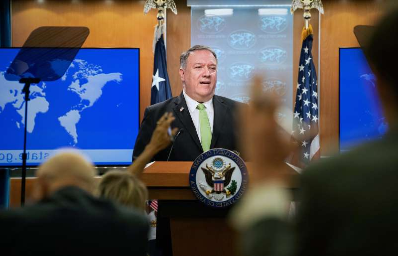 Mike Pompeo sitting at a desk in front of a laptop: Image: