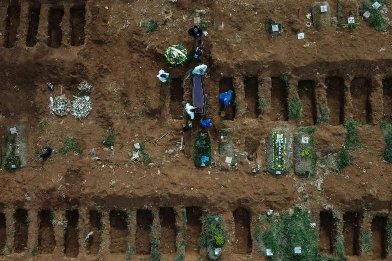 a circuit board with a cake: Aerial picture showing gravediggers burying an alleged COVID-19 victim at the Vila Formosa Cemetery, in the outskirts of Sao Paulo, Brazil
