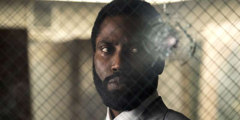 a close up of John David Washington wearing a black shirt: Christopher Nolan movie Tenet has been given a new synopsis along with its second trailer, but it fails to clear up any of the mysteries behind it.