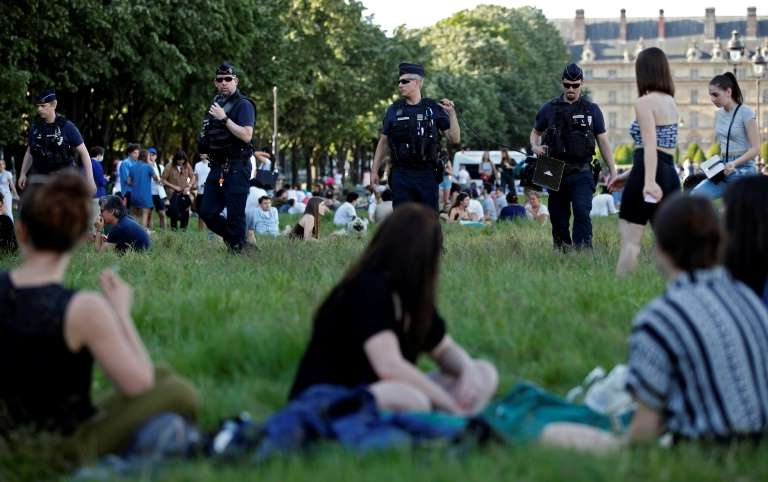 a group of people in a field: The police have been forced to clear the huge open lawns in front of Les Invalides in central Paris of picnickers twice in two days
