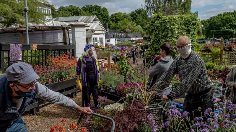 a group of people in a garden: A garden center in London this month. Higher temperatures this week have brought people increasingly outdoors.