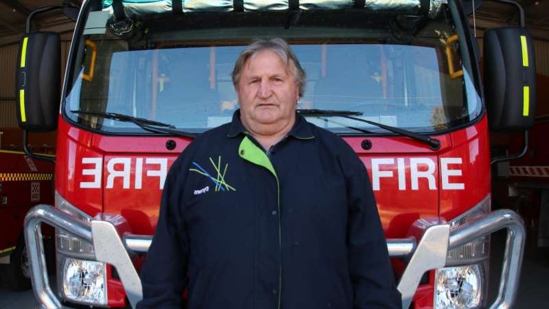 a man standing in front of a bus: Rod Lewis's family was sheltering in the fire station when it caught alight.