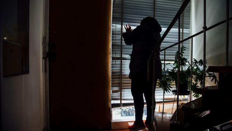 a man standing in front of a window: Domestic violence services say they are seeing signs victims are struggling to get help.