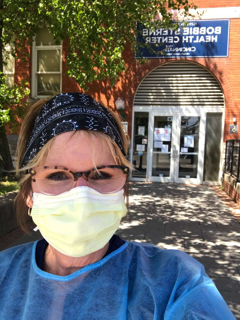 a person standing in front of a building: Deann Ramey sporting her mask while working in downtown CIncinnati.