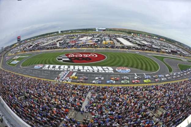 a stadium full of people: FILE - In this May 27, 2018, file photo, the field takes the green flag to start the NASCAR Cup Series auto race at Charlotte Motor Speedway in Concord, N.C. Some fans have been coming to the Coca-Cola 600 for decades, but they wont be allowed into Charlotte Motor Speedwa on Sunday, May 24, 2020, due to Covid-19, leaving the grandstands empty and many disappointed. (AP Photo/Mike McCarn, File)
