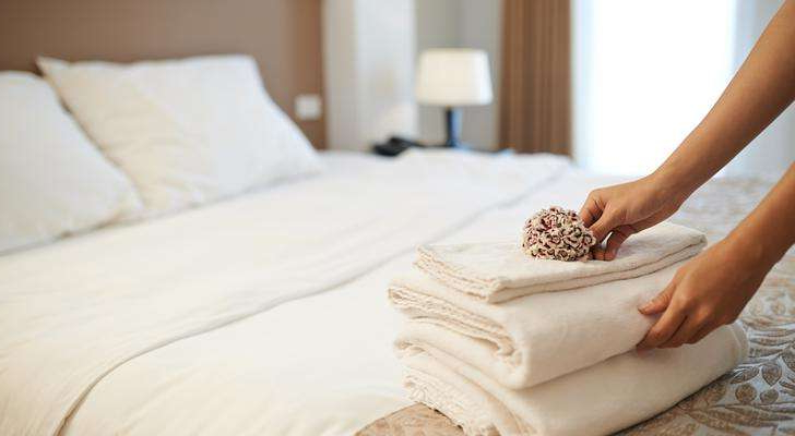 a woman sitting on a bed: hotel room cleaning service