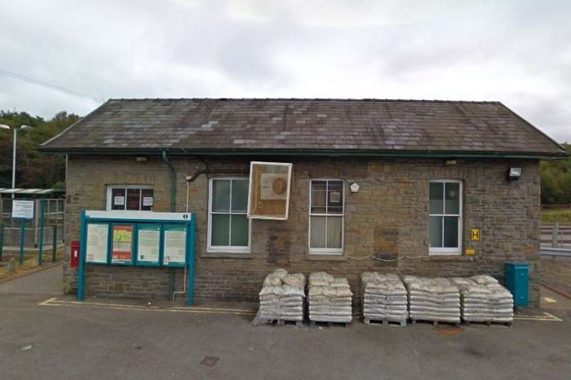 a wooden bench in front of a brick building: The incident happened at Rhymney railway station