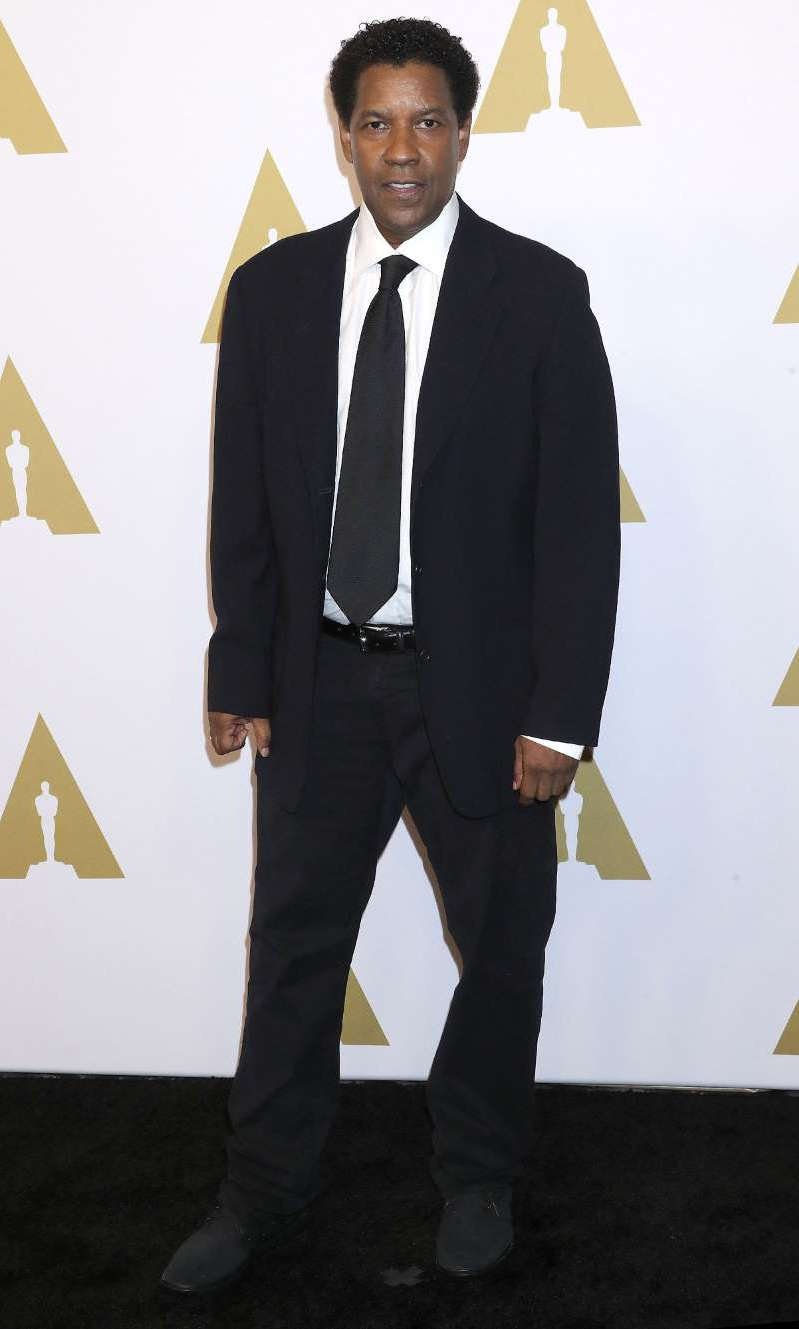 Denzel Washington wearing a suit and tie holding a sign posing for the camera