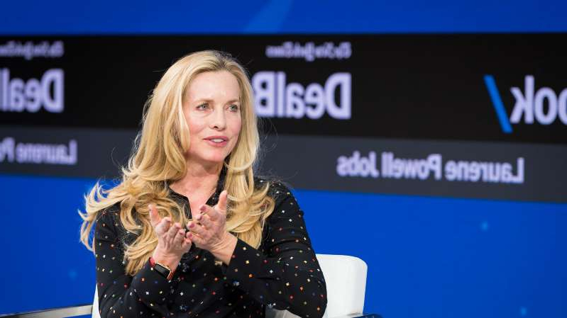 Laurene Powell Jobs standing in front of a stage: Laurene Powell Jobs, the majority owner of the Atlantic, onstage at the New York Times DealBook Conference in 2017.