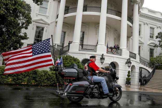 Slide 1 of 50: U.S. President Donald Trump watches as members of Rolling Thunder take part in a ceremonial ride around the South Lawn during an event honoring veterans ahead of the Memorial Day holiday at the White House in Washington, U.S., May 22, 2020. REUTERS/Leah Millis     TPX IMAGES OF THE DAY