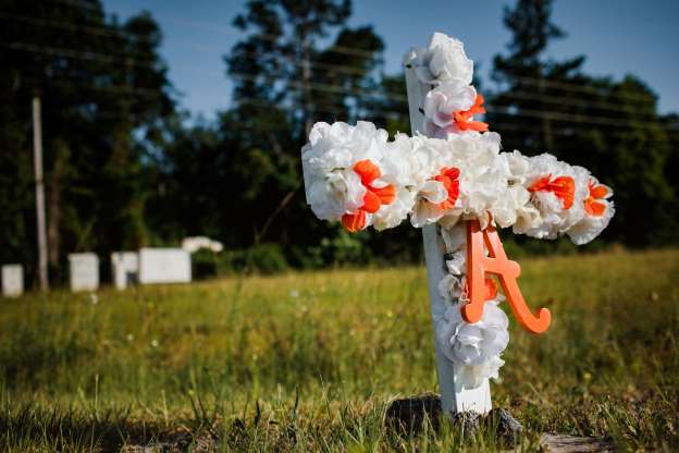a fire hydrant in the middle of a field: A white and orange cross in the Satilla Shores neighborhood where Ahmaud Arbery, an unarmed young black man, was fatally shot.