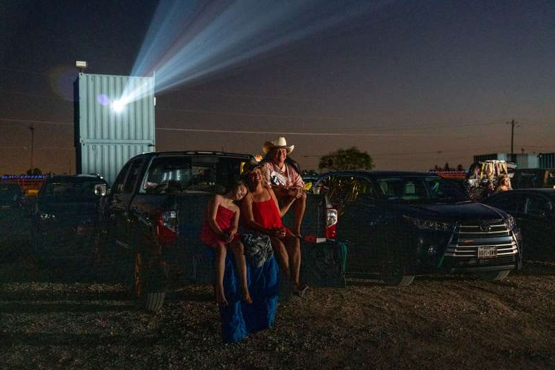 a group of people standing in front of a car: Friends and family watched a screening from their cars at Doc's Drive-In Theater in Buda, Texas, last month.