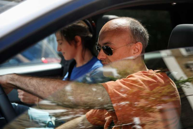 a man sitting in a car: Boris Johnson's chief adviser, Dominic Cummings, and his wife Mary Wakefield leaving his home on May 23, 2020 in London.