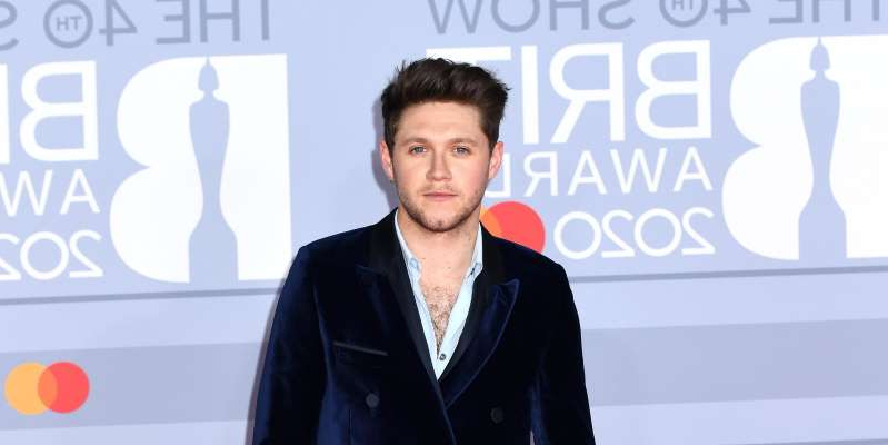 Niall Horan standing in front of a sign: Niall Horan told Jamie Redknapp on Redknapp's Home Fixture that although the band have been