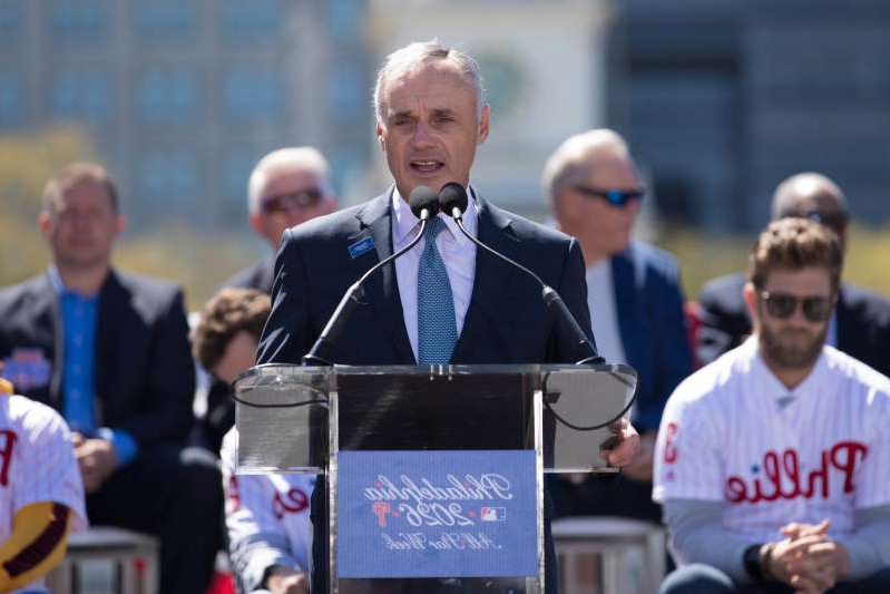 Rob Manfred standing in front of a crowd: The move is one of many the MLB will make to try and recoup lost revenue.