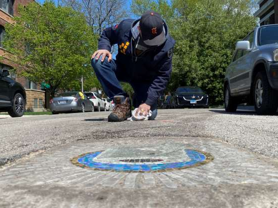 a man riding a skateboard up the side of a road: Chicago artist Jim Bachor creates four pandemic-themed pothole mosaics on the city's North Side