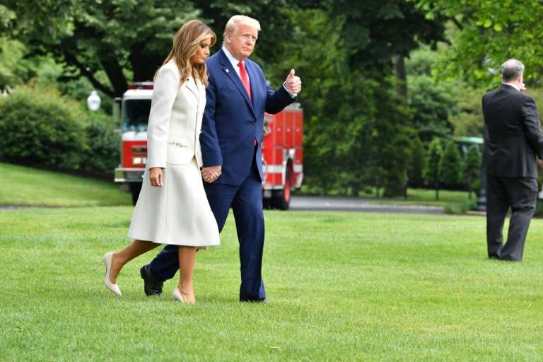 a couple of people that are standing in the grass: US President Donald Trump leaving the White House on May 25 2020 with First Lady Melania