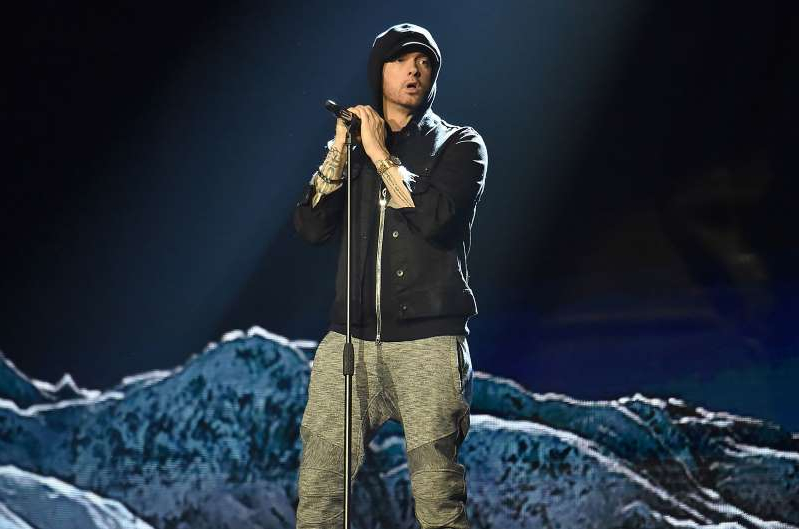 a person that is standing in the snow: Eminem