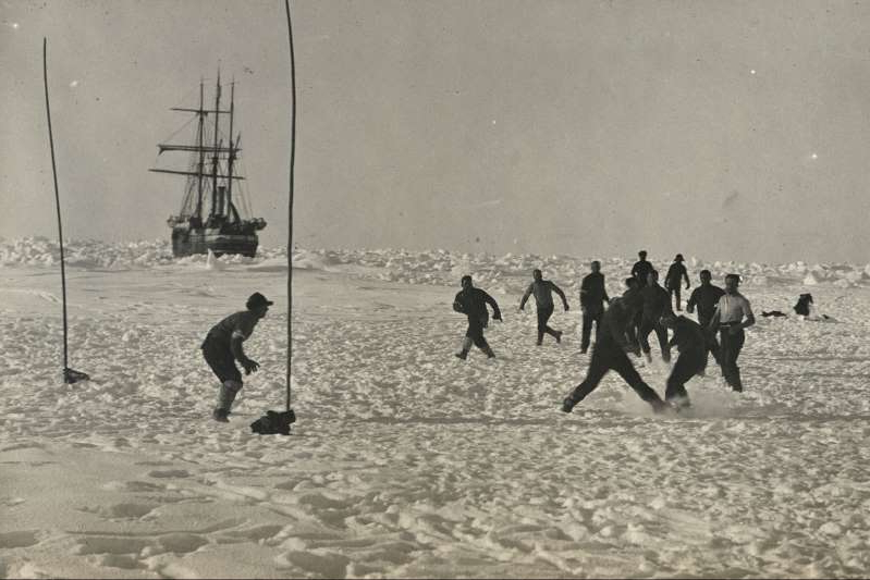 a group of people on a beach: Explorer Ernest Shackleton and his crew faced months of isolation, risk, and uncertainty after their ship Endurance became trapped in pack ice in 1915. Soccer games were one of many diversions Shackleton contrived to keep his men occupied and morale high.
