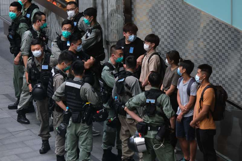 a group of people standing in front of a crowd: Riot police stop and search people in front of a Louis Vuitton luxury goods store in Hong Kong on Wednesday.