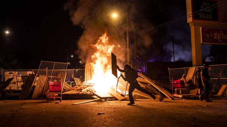a person riding on the back of a fire: Protesters lit fires and burned buildings in Minneapolis overnight Wednesday.