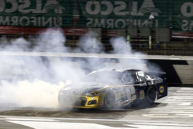 a train on a track with smoke coming out of it: Chase Elliott celebrates after winning at Charlotte on Thursday night. (Photo by Chris Graythen/Getty Images)