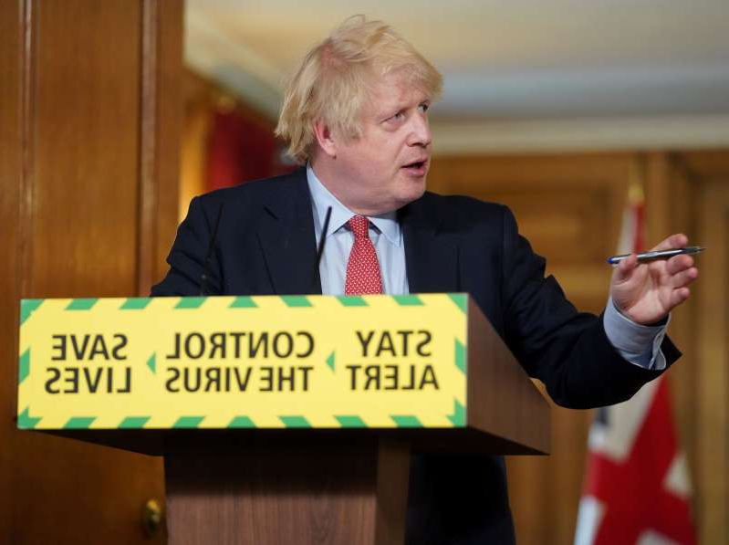 Boris Johnson holding a sign: FILE PHOTO: Daily COVID-19 news conference in London