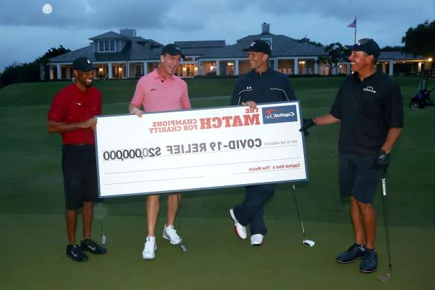 Slide 1 of 26: Tiger Woods and Peyton Manning celebrate after defeating Phil Mickelson and Tom Brady in