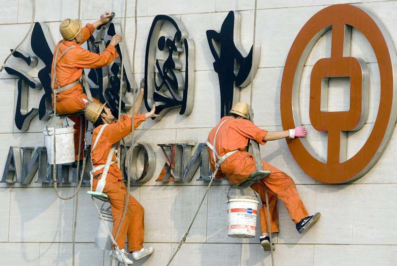 Workers clean a Bank of China logo in Beijing.