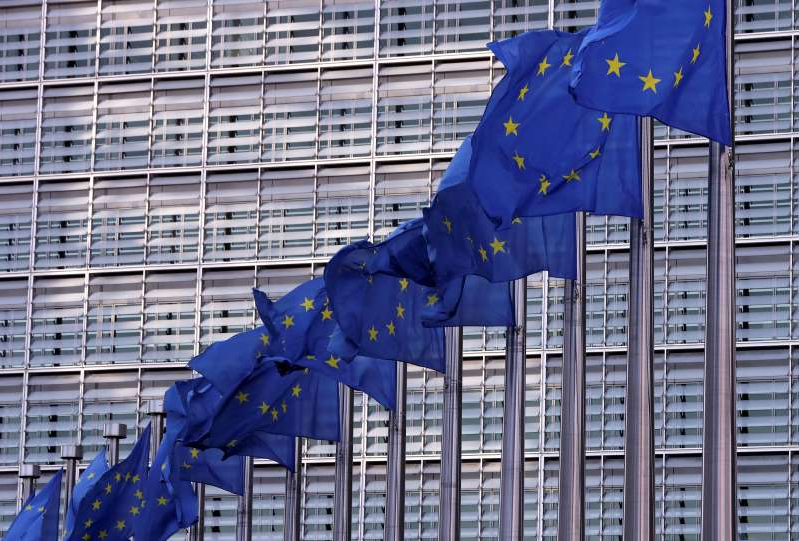 a person standing in front of a building: FILE PHOTO: European Union flags fly outside the European Commission headquarters in Brussels