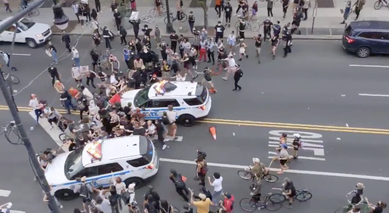 a group of people riding on the back of a car: NYPD cruisers were seen on videos ramming into protesters.