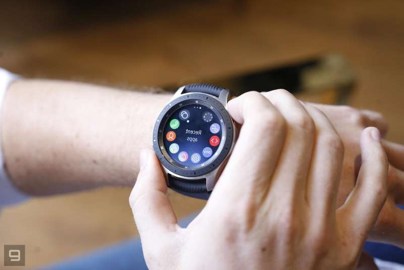 a hand holding a watch: Samsung Galaxy Watch