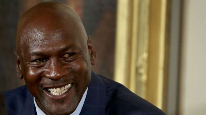 Michael Jordan wearing a suit and tie smiling and looking at the camera