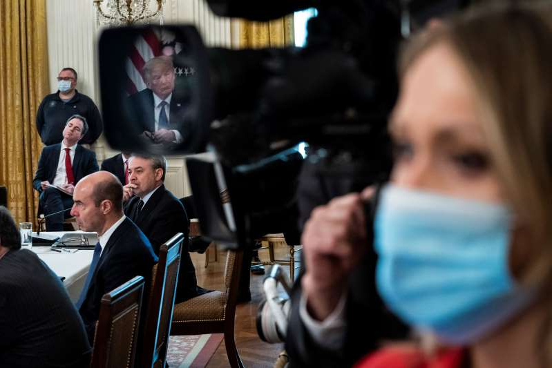 a group of people that are talking to each other: President Trump, reflected in a television camera lens, participates in a socially distant Cabinet meeting on May 19 in the East Room of the White House.
