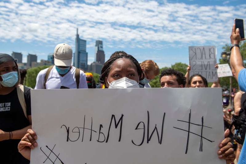 a group of people holding signs: Demonstrators gather on the steps of the Philadelphia Museum of Art Saturday, May 30, 2020 in Philadelphia, Pa.