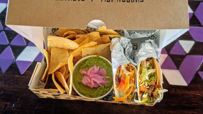 a box filled with different types of food on a table: A Condado Tacos location in Columbus, Ohio, is facing public scrutiny for filling an order for Bud Boxes placed by Ohio Highway Patrol.
