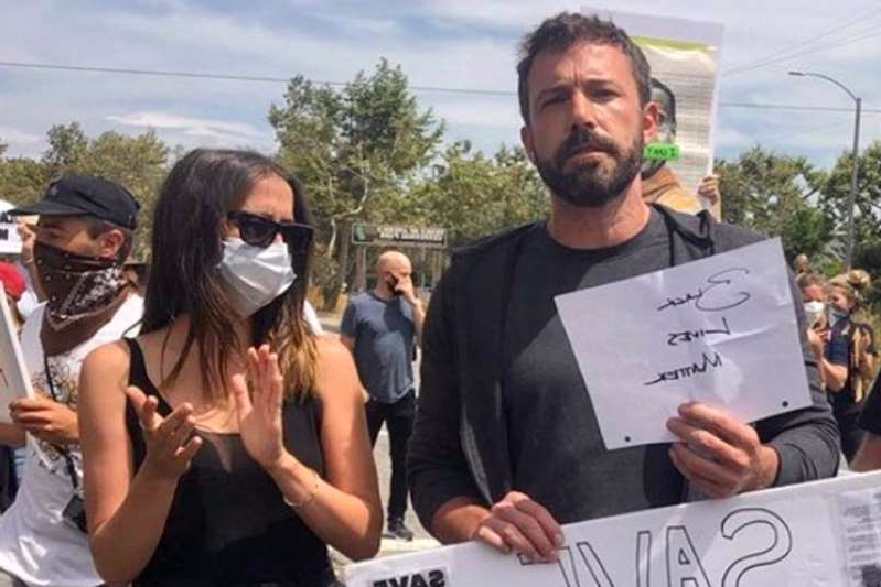 Ben Affleck et al. holding a sign: Ben Affleck and Ana De Armas join Venice, Calif. protests