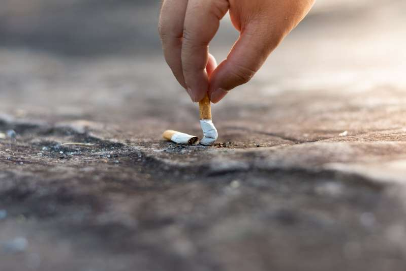 Close-Up Of Hand Extinguishing Cigarette On Floor