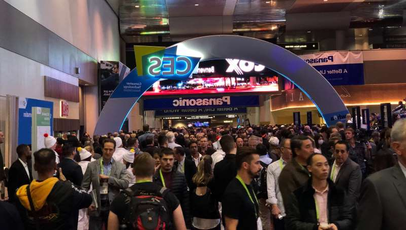 a large crowd of people standing in front of a store: Huge crowds descend upon CES