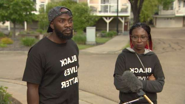 a man standing on a sidewalk: Sifa Ngeze and Jean-Claude Rukundo say there was no reason for the arrest in 2018.