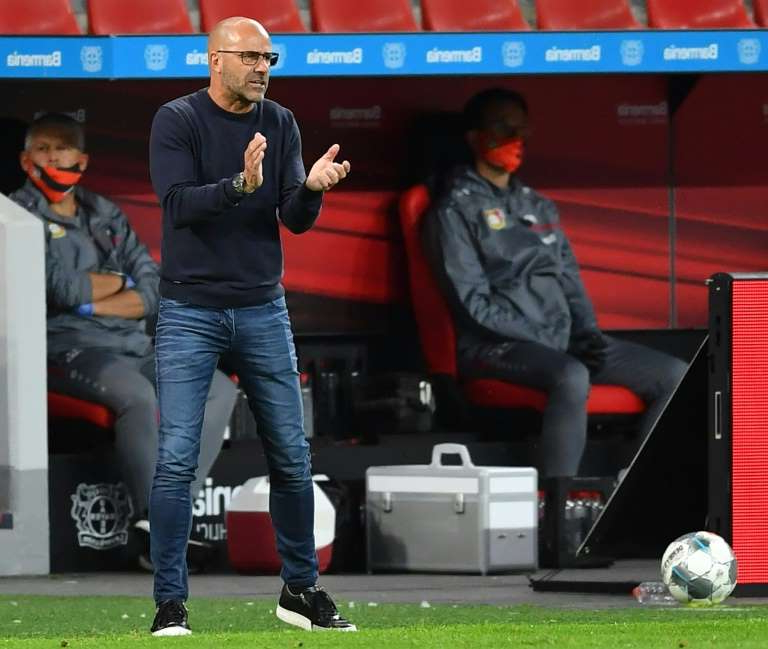 Peter Bosz standing in front of a television: Leverkusen boss Bosz has called for health regulations to be eased in Germany