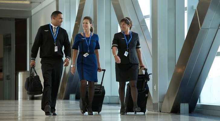 a group of people standing in a room: United flight attendants walk through Houston Bush Intercontinental Airport